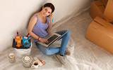 Young woman portrait while painting new apartment ,sitting with laptop