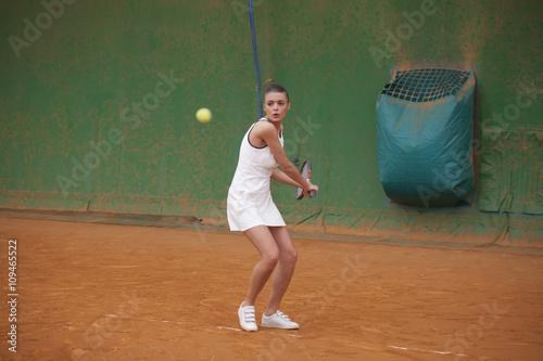 Poster giovane tennista si allena a colpire di rovescio