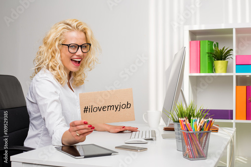 "Woman in office showing ""I love my job"" cardboard"