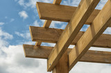 Closeup shot at the corner of a wooden pergola against blue sky