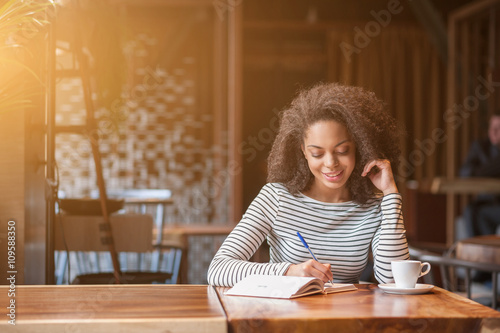 Cheerful young woman is writing in notebook