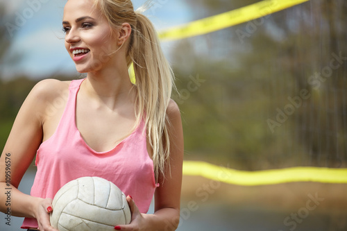 Poster Joyful sexy blond girl playing volleyball outdoors on the lakesi