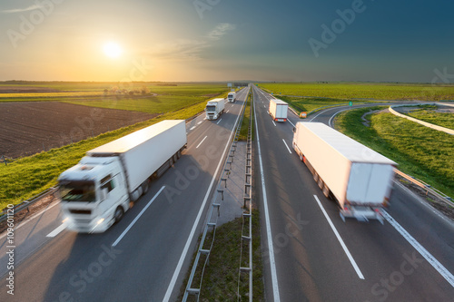 Big white trucks on highway towards the setting sun