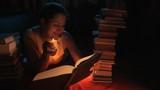 девушка читает книгу со свечей