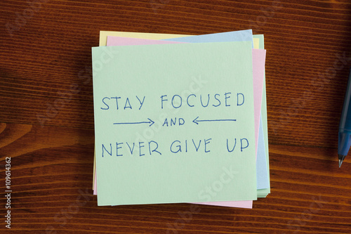 Poster Stay focused and never give up written on note