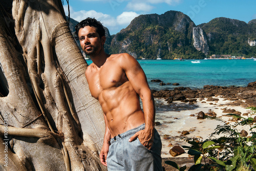 Poster Portrait of gym handsome brunette with nude torso on the beach
