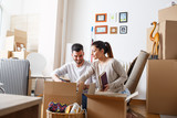 Young couple unpacking cardboard boxes at new home.Moving house. - 109688118