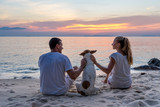 Young couple sitting on a tropical beach with a dog on a sunset  background