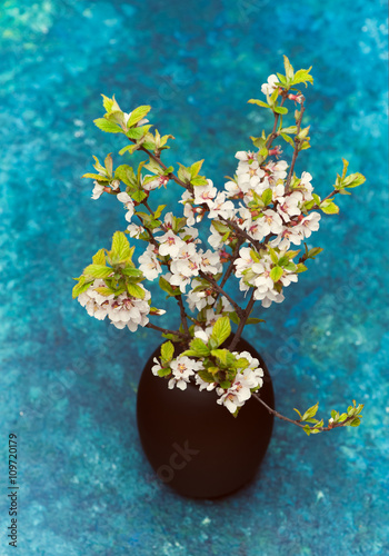 Poster White flowers in vase. branch of cherries.