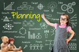 Cute little girl wearing business dress and showing planning concept on green chalk board.