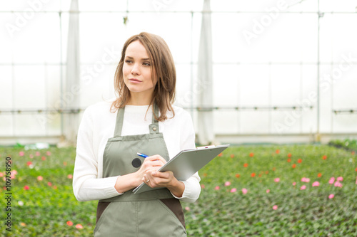 Young attractive woman writing notes at the plants nursery