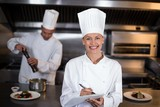Portrait of smiling female chef writing on clipboard