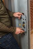 Cerrajero poniendo una cerradura en puerta acorazada.