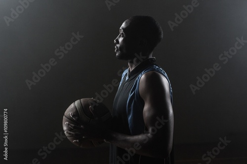Fotobehang Basketbal One side of a basketball player holding a basketball