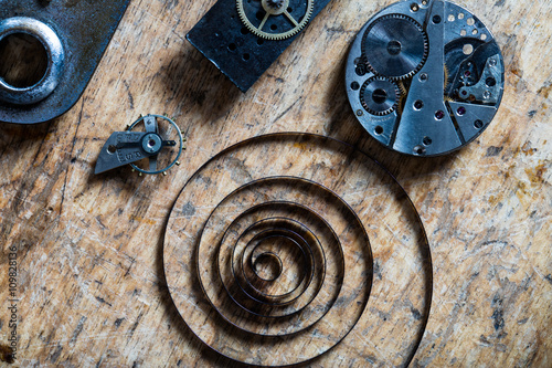 spring, balance wheel and clockworks on a table Poster