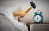 Man smashing alarm clock with sledge hammer