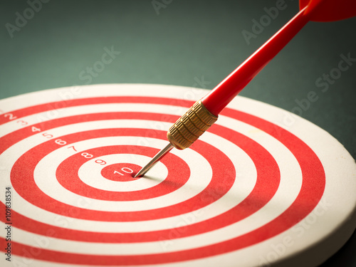 Poster Selective focus of red dart arrow hitting target center of dartboard on black background