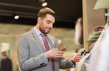 man in suit with smartphone at clothing store