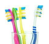 Четыре зубные щетки в стеклянном стакане