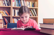 Young Girl Reads a Book in Library