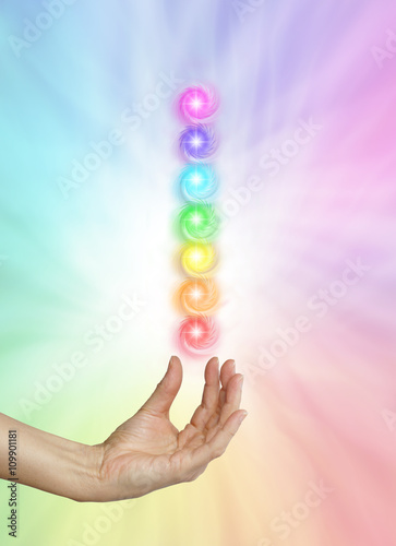 Poster Seven Spinning Chakras on Rainbow colored background - Female healing hand outst