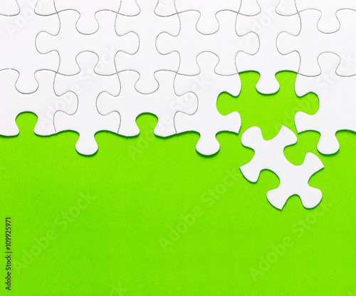 White jigsaw puzzle on green background - 109925971