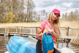 young blonde Caucasian woman hiking in nature by the lake on sun