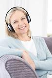 Mature Woman Listening To Music On Wireless Headphones