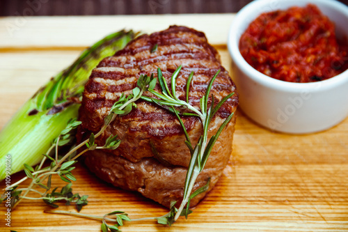 Fototapeta Beautiful juicy well done steak with sauce on a wooden Board