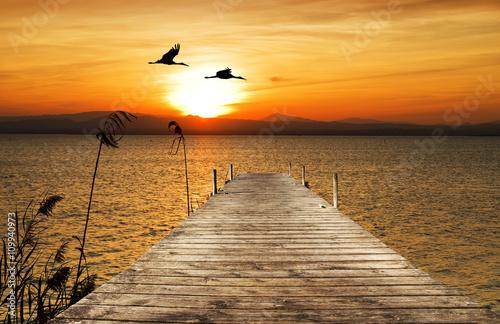 Plagát puesta de sol sobre el embarcadero del mar
