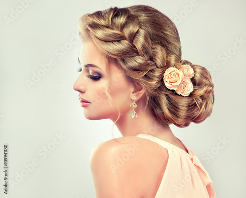 Fototapeta Beautiful model girl with elegant hairstyle . Beautiy woman with fashion wedding hair and colourful makeup