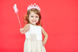 Little princess girl pointing her magic wand towards camera