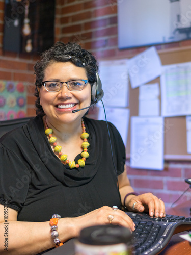 Middle Aged Hispanic Female In Office Environment Wearing Headph Poster