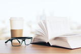 Open book, coffee and glasses