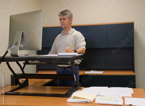 A man is working at a standup desk in an office where he works because standing is healthier than sitting all day. Live healthy, don't sit all day.