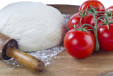 dough, rolling pin and tomatoes