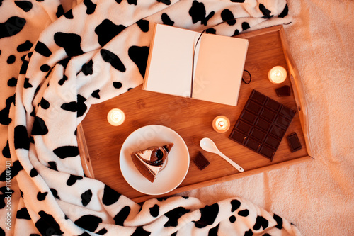 Poster Sweet cake, chocolate bar, candles and notebook in bed on tray