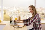 Smiling girl working on laptop