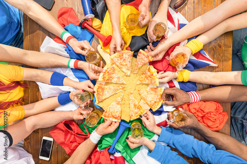 Poster Top view of multiracial hands of football sport supporter sharing pizza - Friend