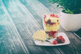 Mascarpone dessert in glass with biscuit, raspberries fruit.