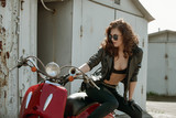 portrait of a beautiful girl in leather jacket, brassiere and glasses near red  motorcycle