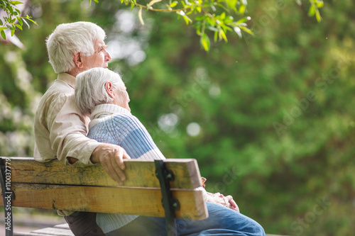 Elderly couple resting on a bench in the park Poster