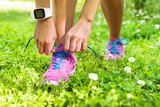 Active lifestyle smartwatch runner woman tying running shoes. Healthy summer living. Sports girl getting ready for weight loss run exercise lacing footwear laces wearing activity tracker wristwatch.
