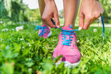 Healthy active lifestyle woman athlete tying running shoes. Happy sporty runner girl lacing shoelaces on pink fashion sneakers on summer grass in city park getting ready for a fitness morning jog.