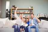 Happy family with arms raised while watching television