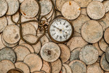 A bunch of coins with a broken pocket watch on top