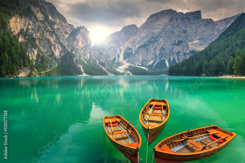 Fotografiet Stunning mountain lake with wooden boats in the Dolomites,Italy