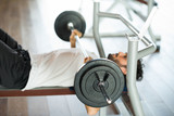 Man lifting a weight on the flat bench