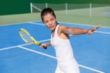 Asian tennis player woman playing hitting forehand in white dress outfit on blue hard court outdoor in summer holding racket. Female athlete determination and concentration concept.