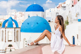 Santorini travel tourist woman on vacation in Oia walking on stairs. Person in white dress visiting the famous white village with the mediterranean sea and blue domes. Europe summer destination.